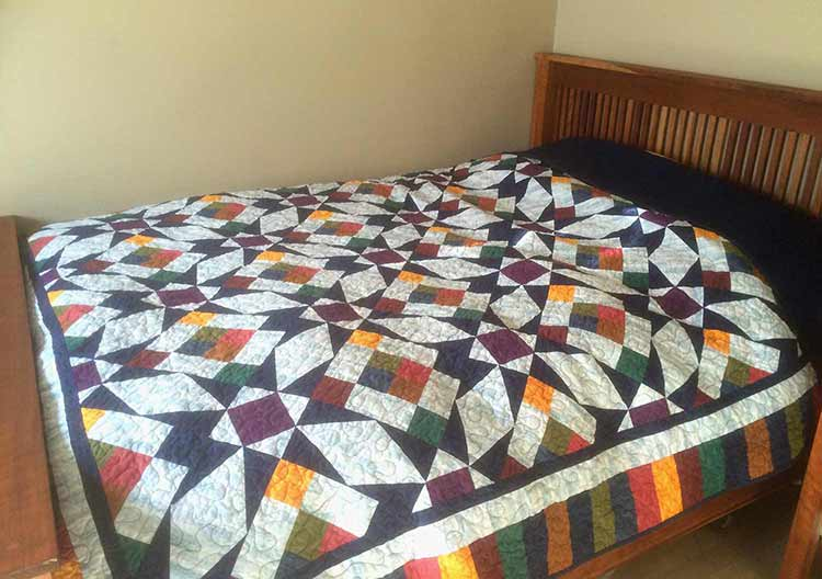 Photograph of a spread quilt on a wooden Arts and Crafts style bed