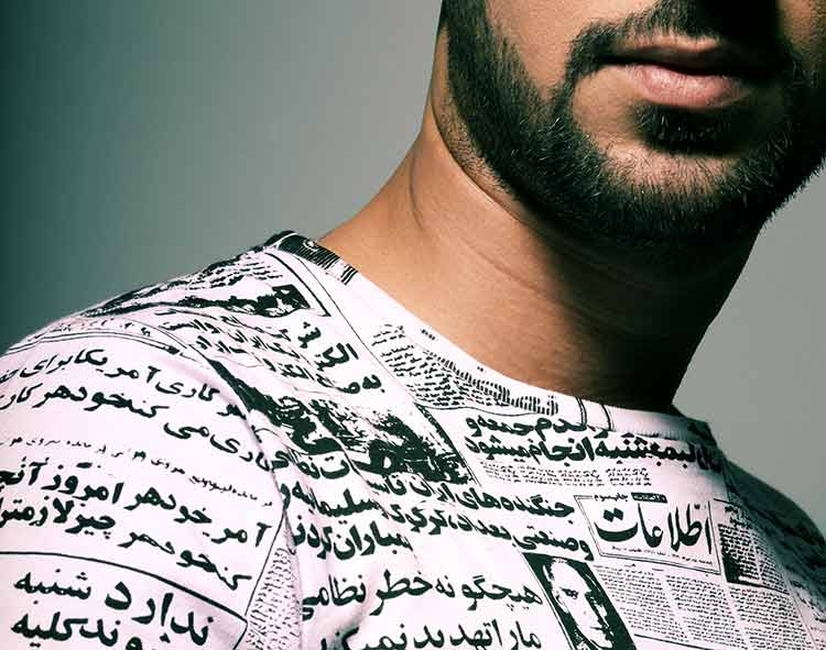 A man wearing a T-shirt printed with Arabic text