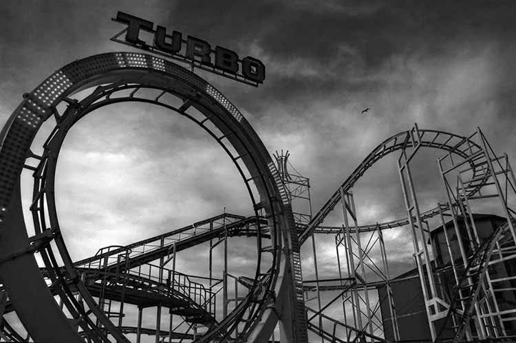 Moody black and white photograph of the rollercoaster at the end of the Brighton Palace pier