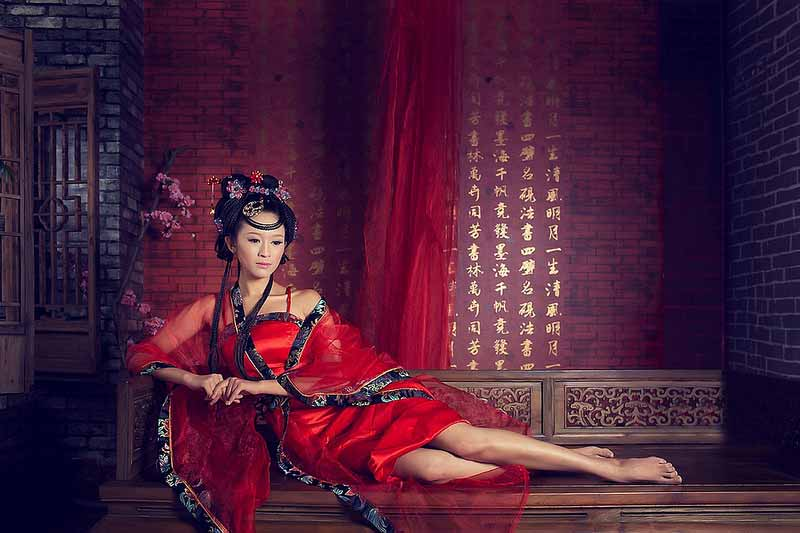 Photograph of a Chinese model dressed as a princess reclining on a wooden bench