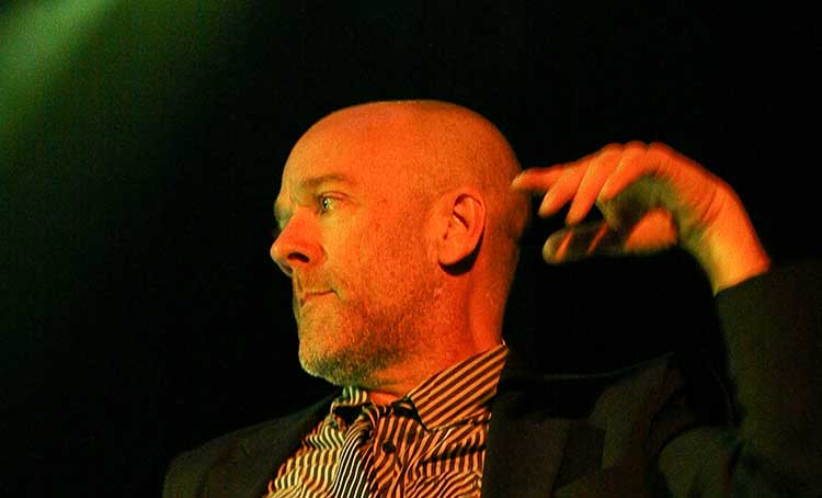 A photograph of Michael Stipe under a green concert light