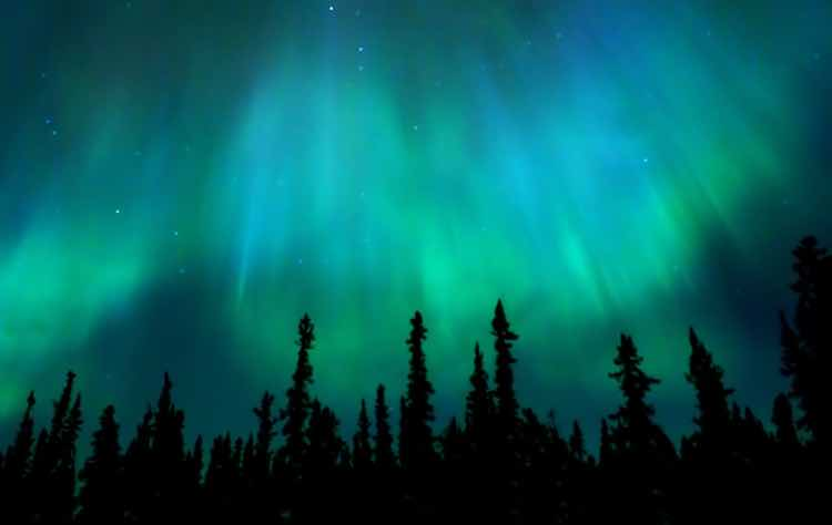 Green curtains of auroae borealis above trees