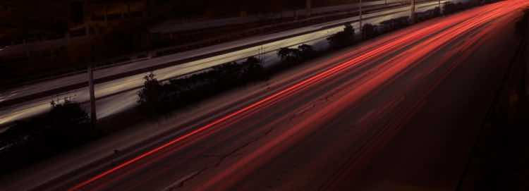 Streaks of red light on a road, caught in a long-expose photograph