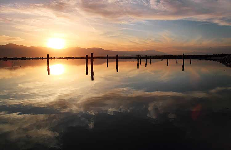The sun setting on the Salton Sea, reflecting the sky and a rotted pier