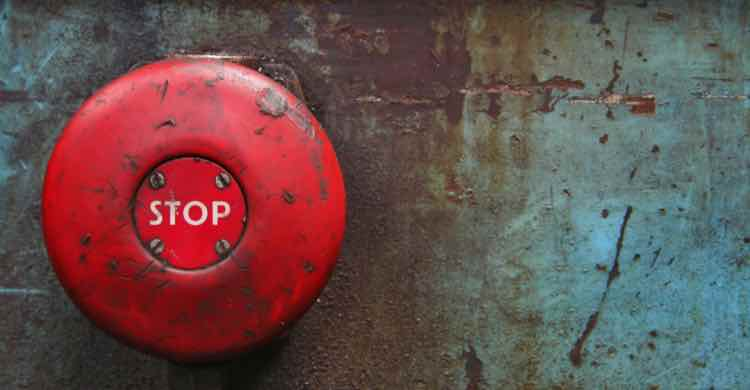 A red stop button on a rusted wall