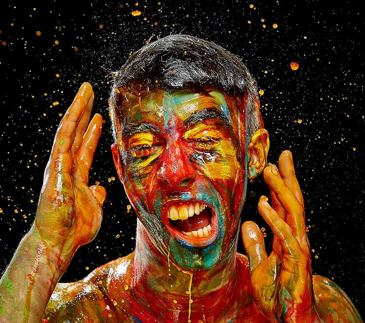 Photograph of an aggressive figure covered in paint