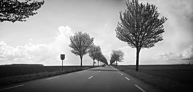 A black and white photograph of a road disappearing into the distance